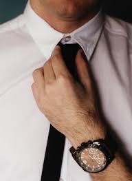 Man tying neck tie looks professional